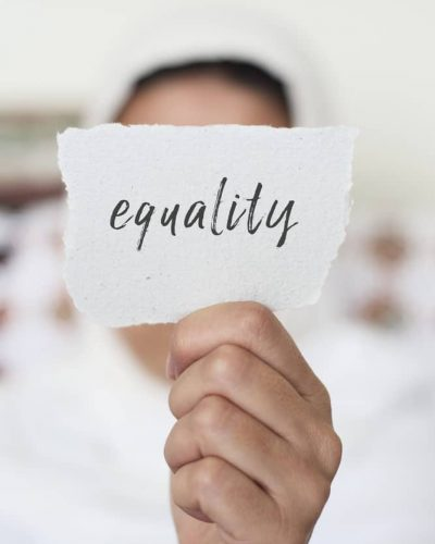 closeup of a young woman indoors wearing a white hijab showing a piece of paper in front of her face with the text equality written in it